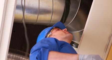 HVAC Tech inspecting air duct work
